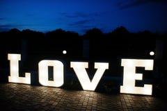 Grand grand mot AMOUR de lettre avec la lumière à l'intérieur au ce de mariage de nuit Photographie stock libre de droits
