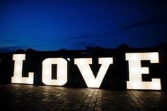 Grand grand mot AMOUR de lettre avec la lumière à l'intérieur au ce de mariage de nuit Image stock