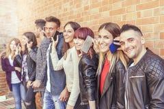 Grand groupe d'amis à l'aide du téléphone intelligent contre un mur rouge Photos libres de droits