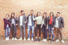 Grand groupe d'amis à l'aide du téléphone intelligent contre un mur rouge Photographie stock