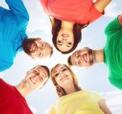 Grand groupe d'amis de sourire restant ensemble et regardant c Image libre de droits