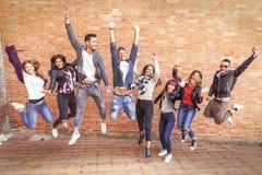 Grand groupe d'amis sautant ensemble pour avoir l'amusement Photographie stock libre de droits