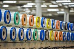 Grand groupe de cônes d'amorçage de bobine sur une machine se faussante dans un moulin de textile Photographie stock