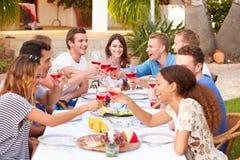 Grand groupe de jeunes amis appréciant le repas extérieur ensemble Photographie stock