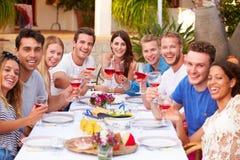 Grand groupe de jeunes amis appréciant le repas extérieur ensemble Images stock