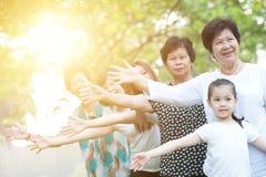 Grand groupe de la famille multi asiatique de générations jouant dehors Image stock