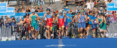 Grand groupe de triathletes fonctionnant dans la zone de transition photos stock