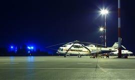 Grand hélicoptère de transport de fret dans le parking à l'aéroport la nuit parmi les lumières Image libre de droits