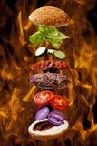 Grand hamburger de barbecue de lard sur le gril de flamme du feu Photographie stock libre de droits