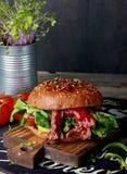Grand hamburger de viande sur le conseil en bois Photo libre de droits