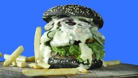 Grand hamburger juteux avec le petit pain noir arrosé avec le sésame avec des verts et le petit pâté de viande entouré par des po images libres de droits