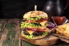 Grand hamburger juteux avec les légumes et le boeuf frits de pomme de terre sur le fond en bois noir de rustick Cru modifié la to Image libre de droits