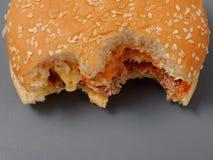 Grand hamburger mordu avec du fromage et la tomate de côtelette sur un fond gris image libre de droits