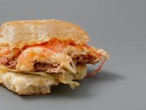 Grand hamburger mordu avec du fromage et la tomate de côtelette sur un fond gris photos libres de droits
