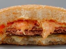 Grand hamburger mordu avec du fromage et la tomate de côtelette sur un fond gris photo stock