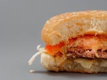Grand hamburger mordu avec du fromage et la tomate de côtelette sur un fond gris photographie stock libre de droits
