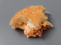 Grand hamburger mordu avec du fromage et la tomate de côtelette sur un fond gris images libres de droits