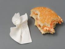 Grand hamburger mordu avec du fromage et la tomate de côtelette sur un fond gris images stock