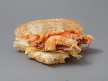 Grand hamburger mordu avec du fromage et la tomate de côtelette sur un fond gris image stock