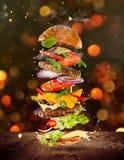 Grand hamburger savoureux avec des ingrédients de vol Images stock