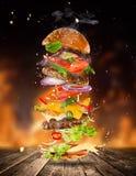 Grand hamburger savoureux avec des ingrédients de vol Images libres de droits