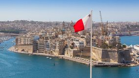 Grand Harbour, Malta, with Maltese Flag. Senglea fortified city and Fort Saint Michael across Grand Harbour from Valletta, Malta. The photo incorporates a Stock Photography