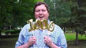 Grand homme tenant les ballons d'or rendant le nombre 1000 extérieur 0th partie de célébration d'anniversaire banque de vidéos