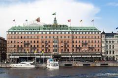 Grand Hotel famoso Estocolmo con un yate y un barco turístico delante de él imagenes de archivo