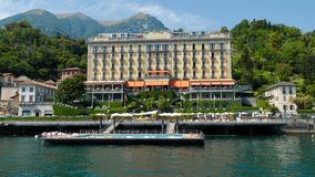 Grand Hotel Tremezzo Lake Como Italy. Water pain of view POV of this historic luxury hotel on Italy`s Lake Como. The Grigne mountains provide a picturesque royalty free stock photo
