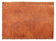 Grand insigne vide, étiquette en cuir granuleuse naturelle vide de jeans de label, fond rustique de macro de modèle Images libres de droits