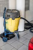 Grand jaune technique d'aspirateur à la station de lavage images stock