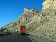 Orange semi truck drives past cliffs Stock Photography