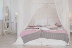 Grand lit avec la literie en pastel mignonne chez la pièce du ` s de la femme Chambre à coucher moderne dans des couleurs en past Photographie stock libre de droits