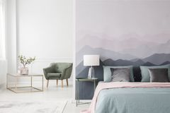 Grand lit par le papier peint de paysage images stock