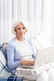 Grand-mère à l'aide de l'ordinateur portable Photo stock