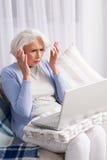 Grand-mère à l'aide de l'ordinateur portable Photographie stock libre de droits
