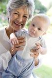 Grand-mère à l'extérieur sur le patio avec la chéri Photographie stock libre de droits