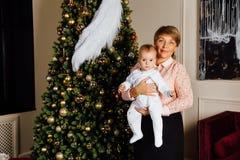 Grand-mère élégante avec un enfant dans des ses bras sur le fond d'un arbre de Noël Image libre de droits