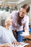 Grand-mère adolescente apportant à grand-mère la boisson chaude Photographie stock