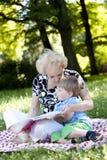Grand-mère affichant le livre à son petit-fils Images libres de droits