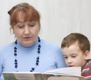 Grand-mère affichant un fils de livre. Photos stock