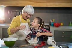 Grand-mère ajoutant l'eau tandis que la petite-fille mélange la farine dans une cuvette Photographie stock libre de droits