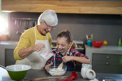 Grand-mère ajoutant l'eau tandis que la petite-fille mélange la farine dans une cuvette Photos stock