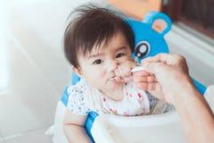 Grand-mère alimentant le bébé asiatique mignon avec une cuillère Images libres de droits