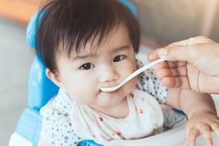 Grand-mère alimentant le bébé asiatique mignon avec une cuillère Image stock