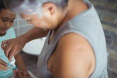 Grand-mère appliquant la pâte dentifrice sur la brosse de petite-filles dans la salle de bains Image libre de droits