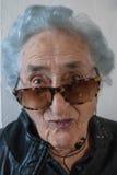 Grand-mère avec des lunettes de soleil, des écouteurs et la veste en cuir Image libre de droits