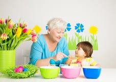 Grand-mère avec des oeufs de pâques de couleur de petit-fils Photo stock