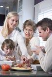 Grand-mère avec la famille mangeant le déjeuner dans la cuisine Photos libres de droits