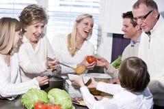 Grand-mère avec la famille riant dans la cuisine Image libre de droits